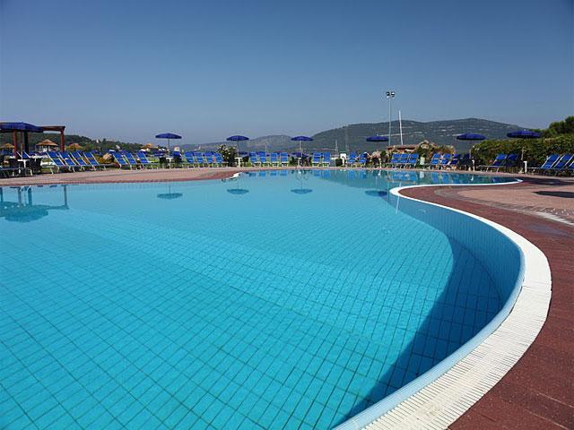 Zwembad met ligstoelen en parasols rondom